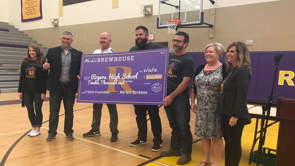No-Li Brewhouse presents Rogers High School with $12,000 check for new football uniforms