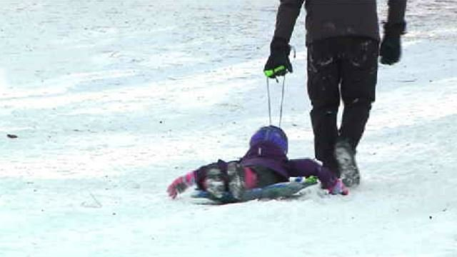 Dozens of families brave bad roads, gusty winds for sledding