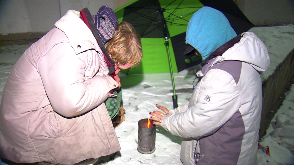Two homeless people in Spokane find warmth from a can fire