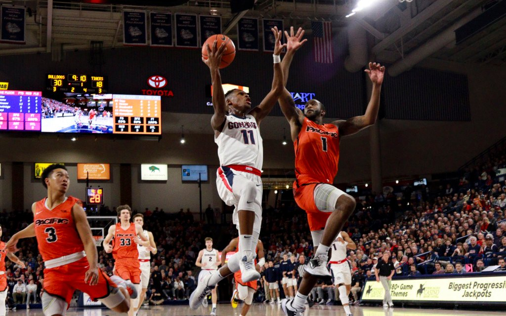 Gonzaga's Joel Ayayi gives Pacific's Austin Vereen a high-five while driving to the hoop.