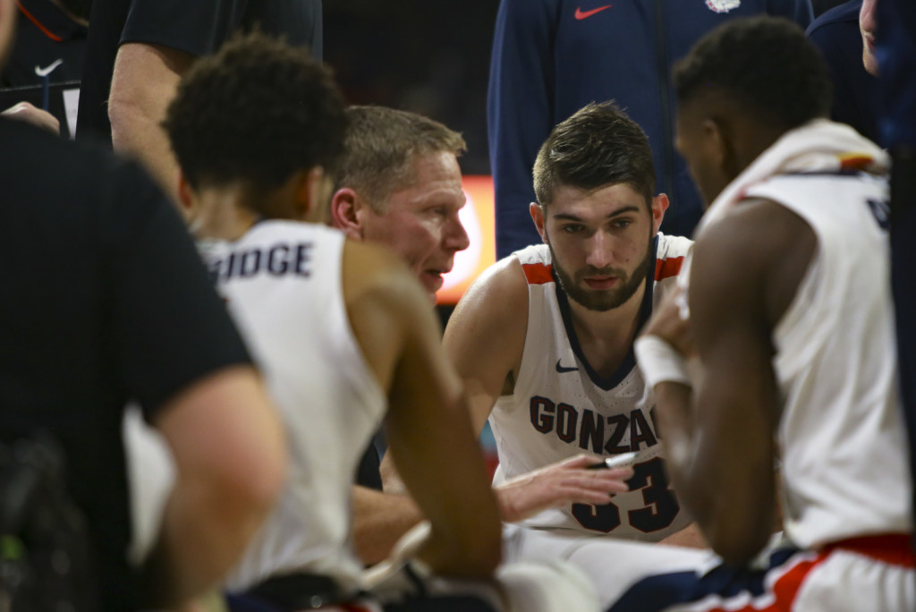 Gonzaga's Killian Tillie listen to coach Mark Few during a timeout.
