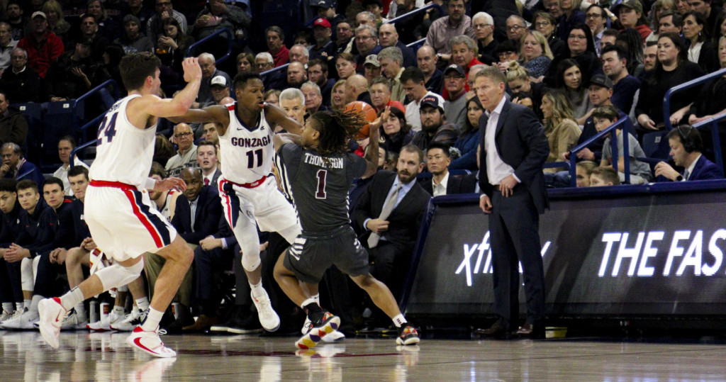 Gonzaga's Joel Ayayi steals the ball from a Santa Clara player while Gonzaga coach Mark Few looks on with approval.