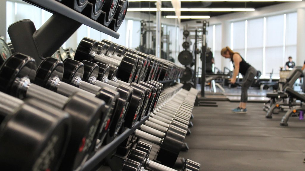 A woman works out by a rack of dumbbells.