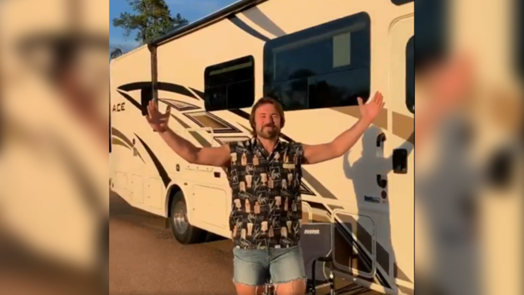 Gardner Minshew, clad in jorts, stands in front of his RV.