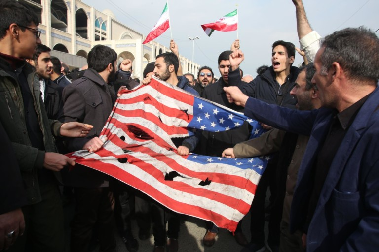 Torn flag held by Iranian protestors