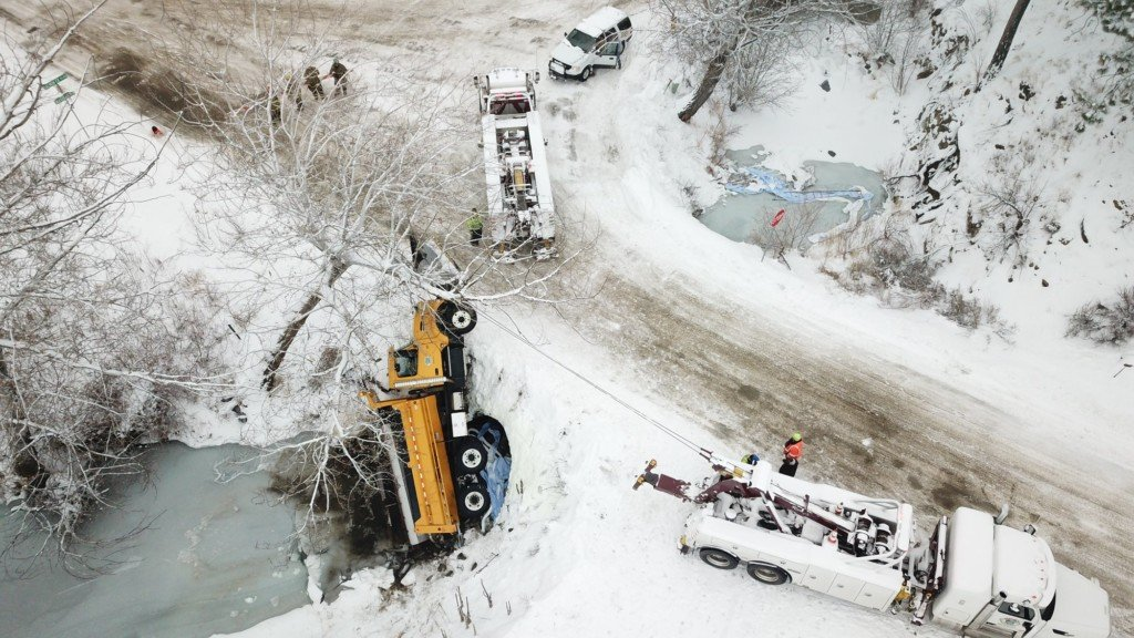 Okanogan County snow plow sits partially in Salmon Creek.
