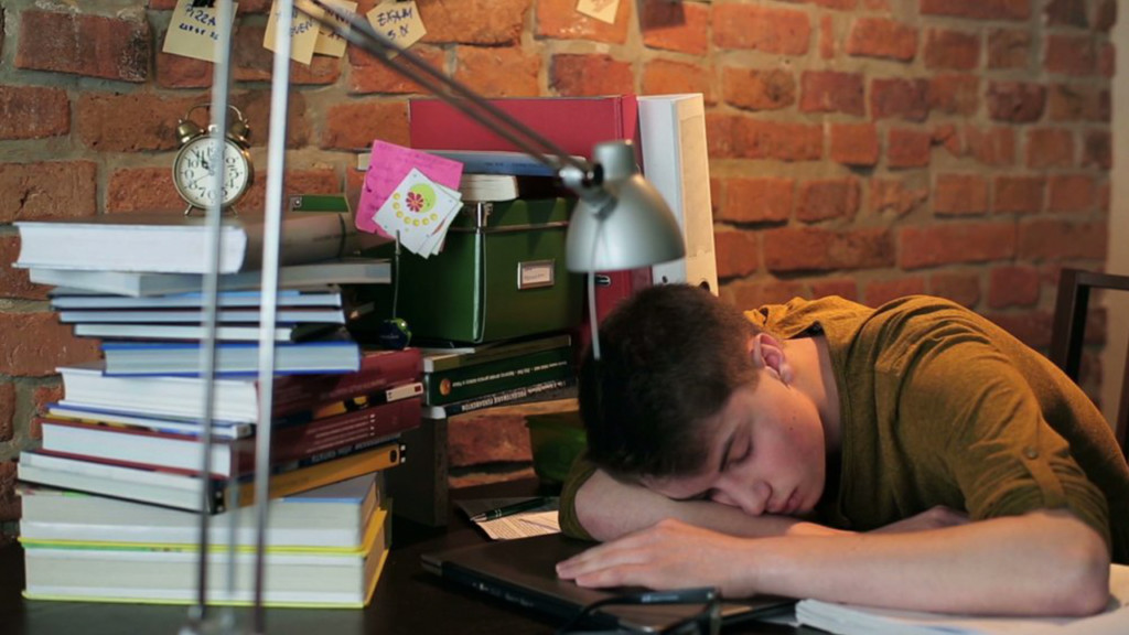 A student sleeping on books
