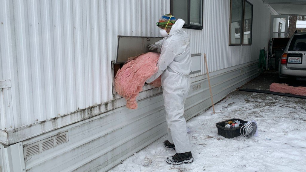 SNAP worker putting insulation into home