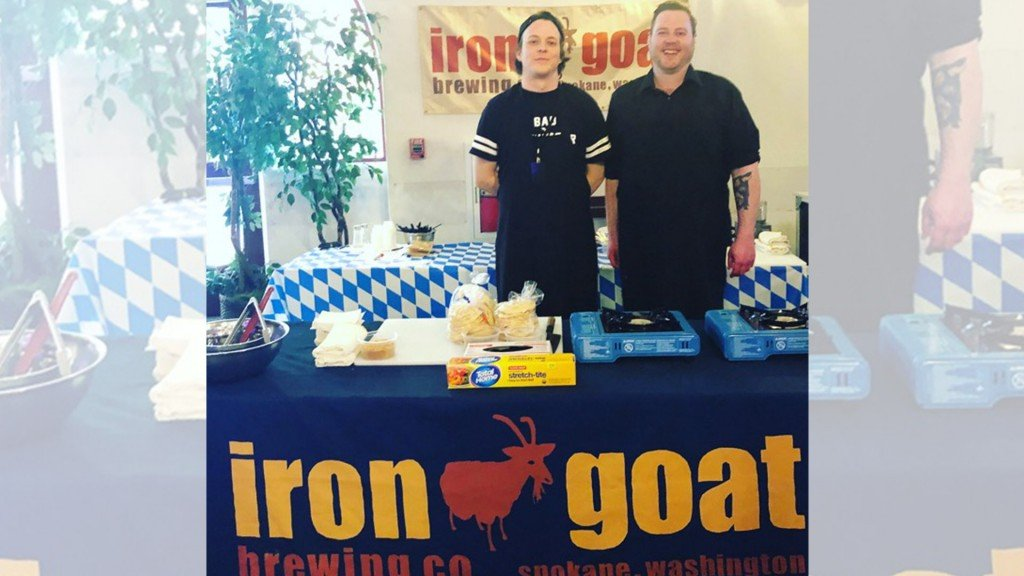 Travis Tveit and Teague Hatsch stand in front of an Iron Goat Brewing sign