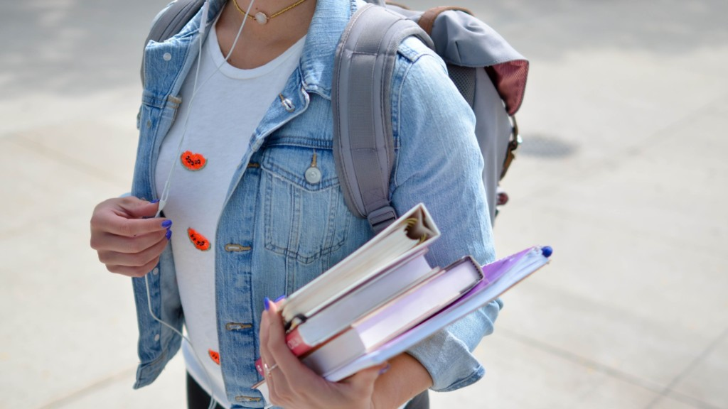 College student holds books.