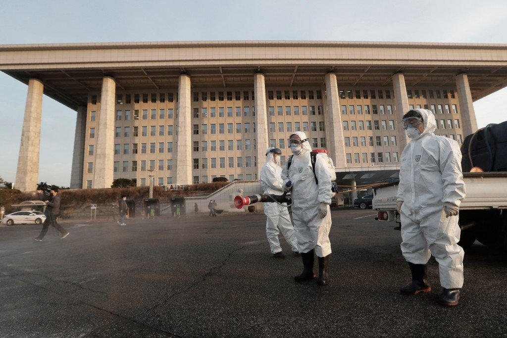 Workers wearing protective suits spray disinfectant as a precaution against the coronavirus at the National Assembly in Seoul.