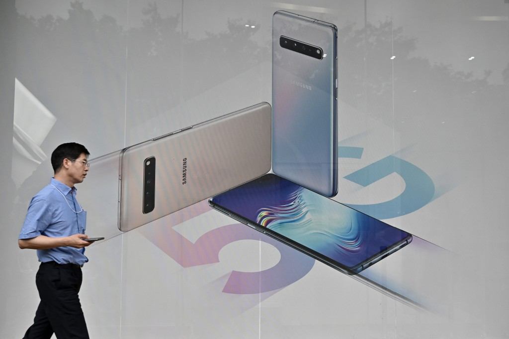 A man walks past an advertisement for the Samsung Galaxy S10 5G smartphone in Seoul on July 31, 2019. - The world's biggest smartphone and memory chip maker Samsung Electronics on July 31, reported second quarter net profits slumping by more than half in the face of a weakening chip market, and as a trade row builds between Seoul and Tokyo.