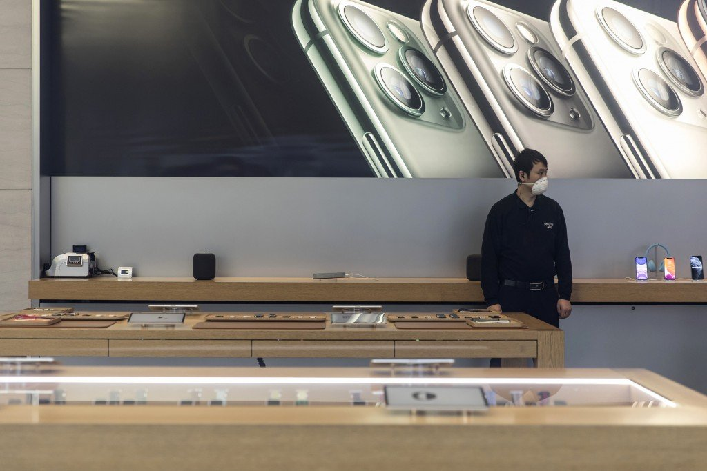 A security guard wearing a protective mask stands guard inside an Apple Inc. store in Shanghai.