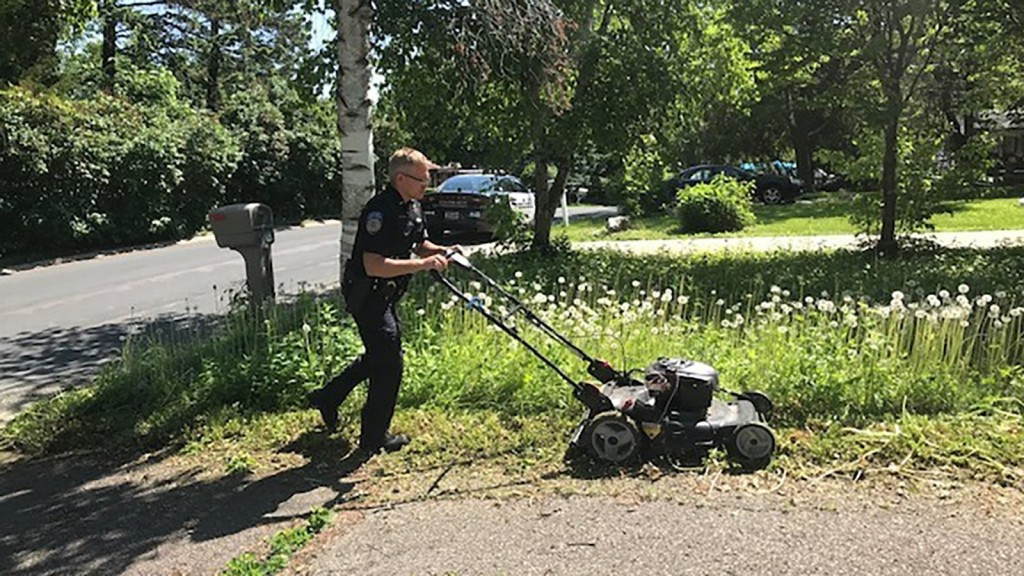 Officer checking on elderly woman mows her overgrown lawn