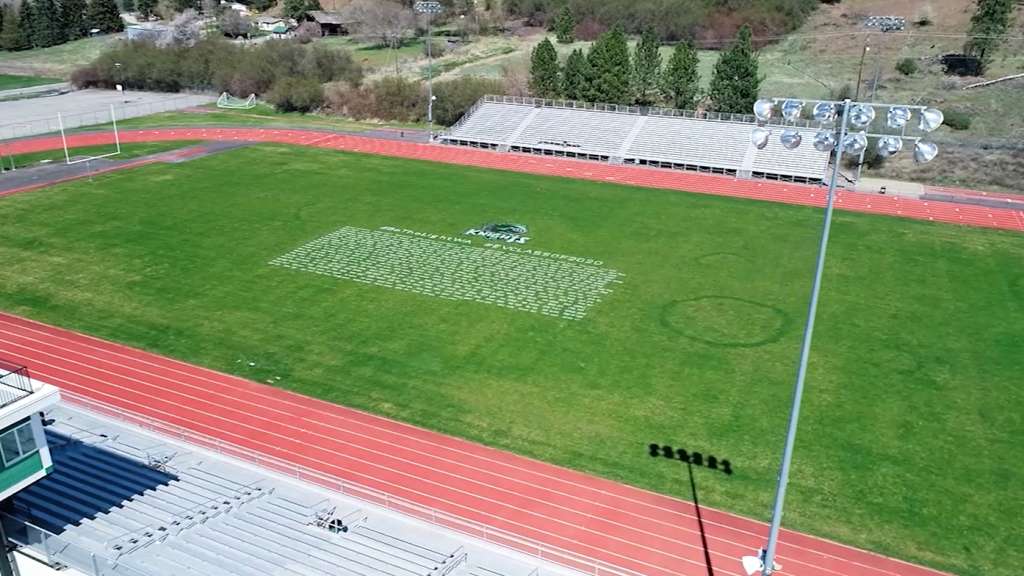 A local artist is hand-painting the names of local high school seniors onto their school football fields