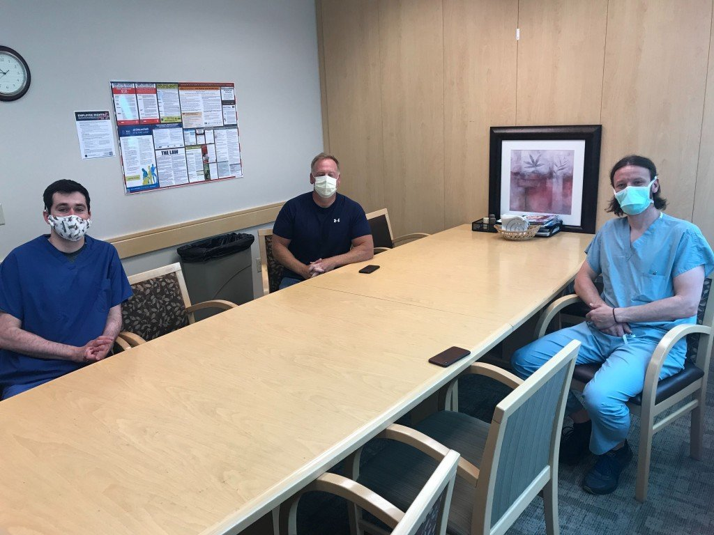 Two Doctors With Cancer Patient Sitting Around Table