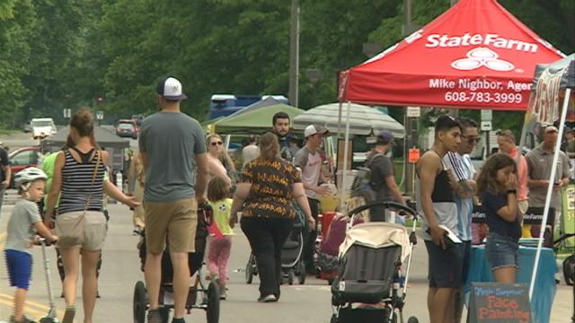 A downtown street fills with people, pets and parades during Open Streets