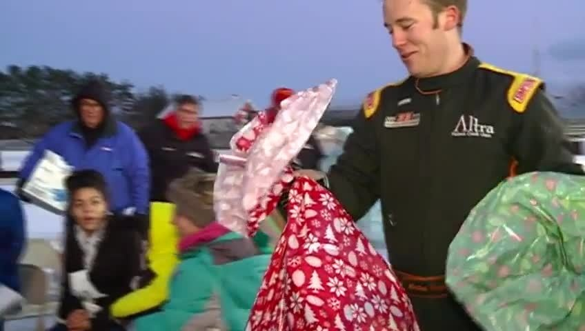 Racecar driver surprises two local families with Christmas gifts