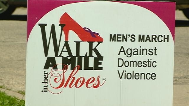 Men walk in high heels against domestic violence
