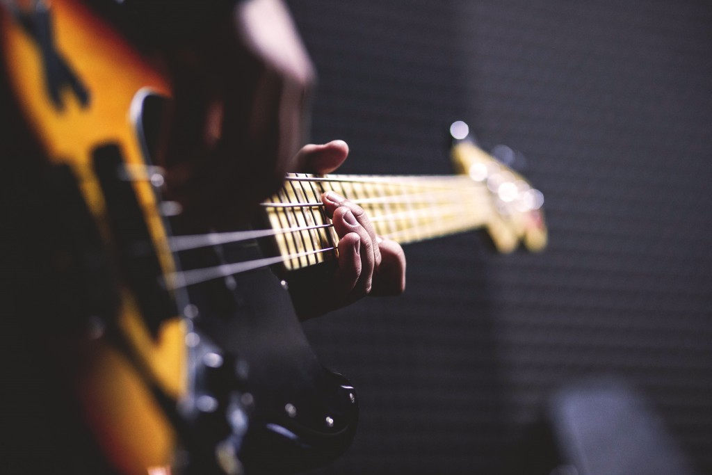 Person Playing Sun Burst Electric Bass Guitar In Bokeh 96380