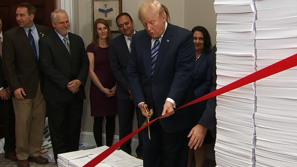 Trump literally cuts the red tape on regulations
