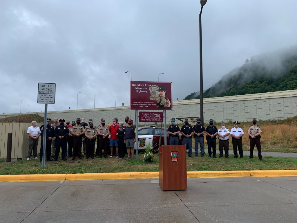 Law Enforcement Officials and Ted Foss' family stand near a sign to remember the 20th anniversary of his death.