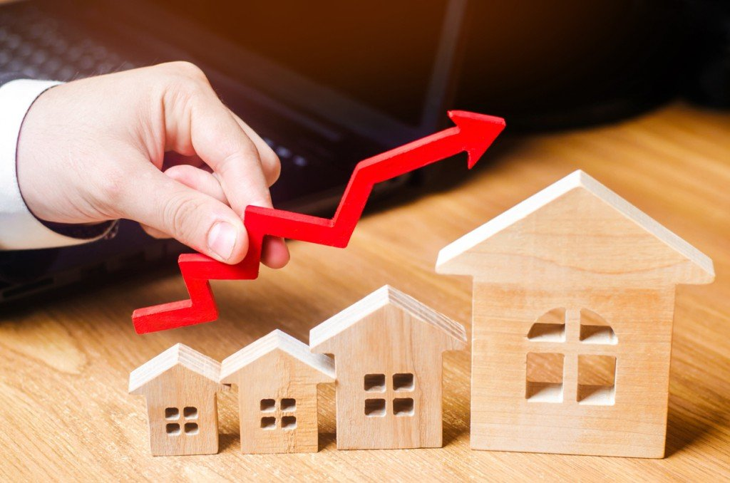 Wooden Houses Stand In A Row From Small To Large With A Red Arrow Up. Concept Of High Demand For Real Estate. Increase Energy Efficiency Of Housing. Rise In House Prices. Property. Businessman's Hand
