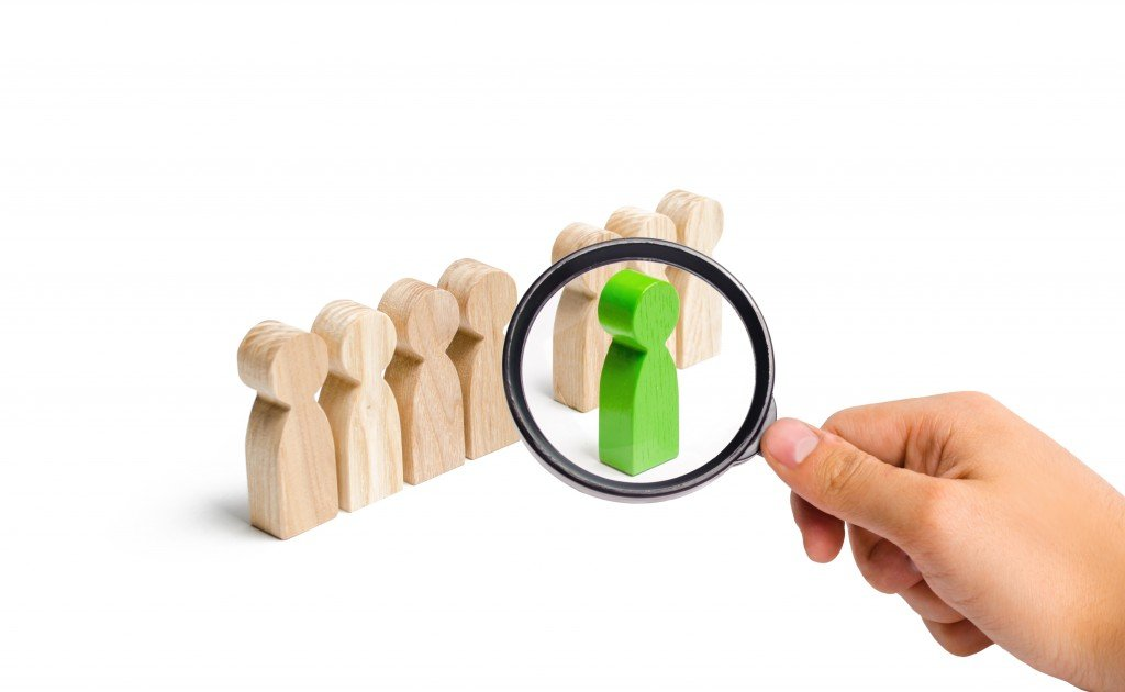 Magnifying Glass Is Looking At The Green Figure Of A Man Comes Out Of The Line Of People. Concept Of Success And Improvement In Work, The Universal Recognition Of Efficiency And Leadership Qualities.