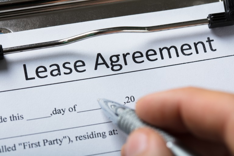 Human Hand Filling Lease Agreement Form