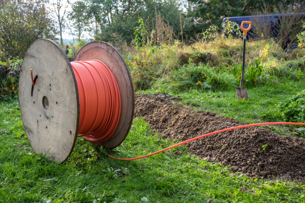 Wooden Spool With Fiber Optic Cable For Fast Internet Ready To Be Laid In Narrow Trenches In The Ground On A Meadow, Infrastructure Expansion In The Countryside