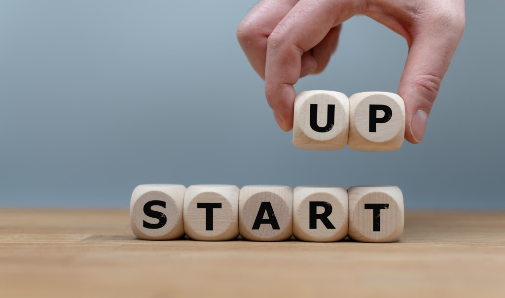 "Cubes Form The Words ""start Up"" While To Fingers Lift The Letters ""up"" In The Air. Cubes Are On A Wooden Table In Front A Grey Background."