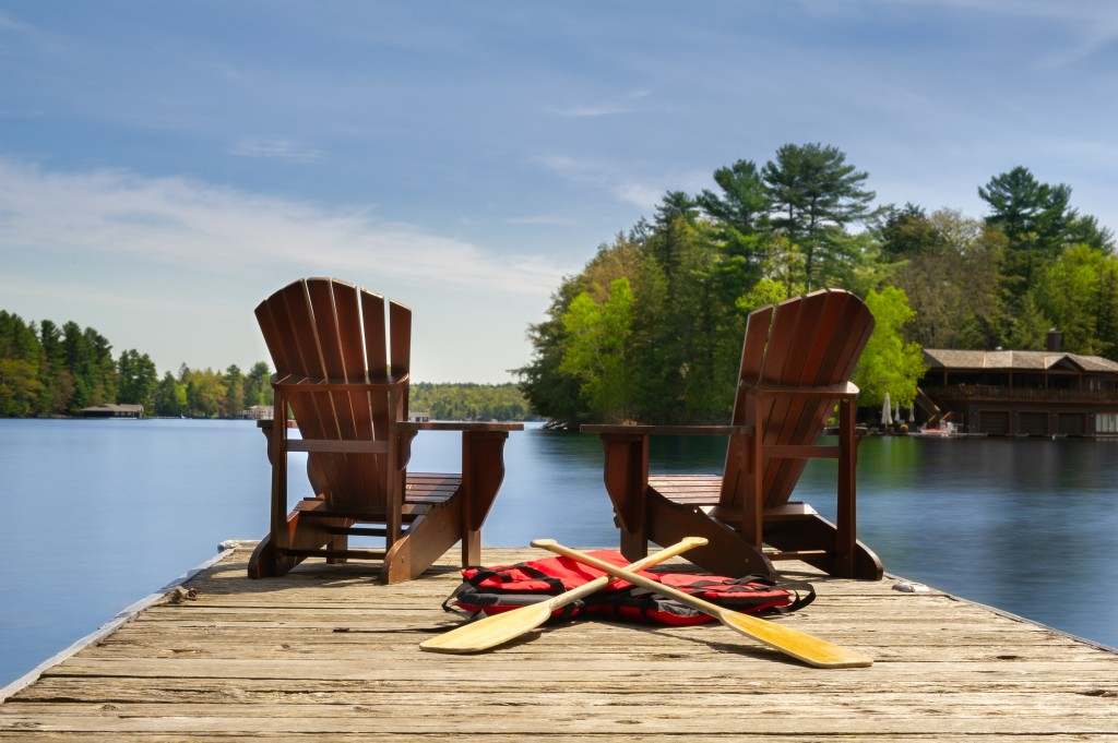Adirondack Chairs On A Wooden Dock Facing Ta Calm Lake