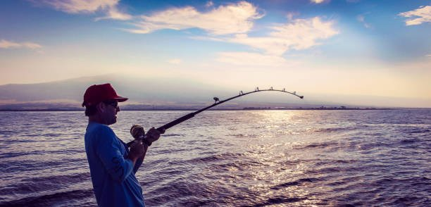 Man With Fisher Rod In Almost Silhouette Against A Vivid Sky