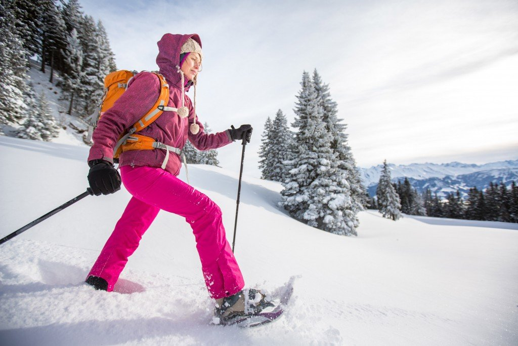Pretty, Young Woman Snowshoeing In High Mountains