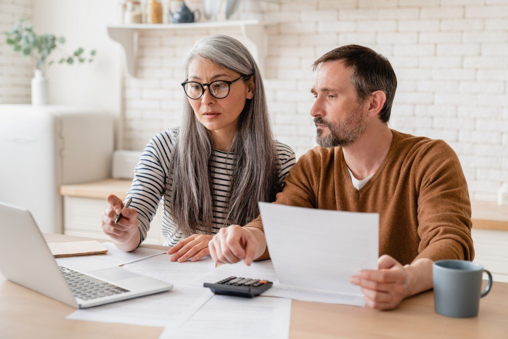 Mature Middle Aged Couple Family Wife And Husband Counting Funds, Savings Declarations, Investments,paperwork, Financial Documents, Bankruptcy, Court Case, Bills, Pension With Laptop.