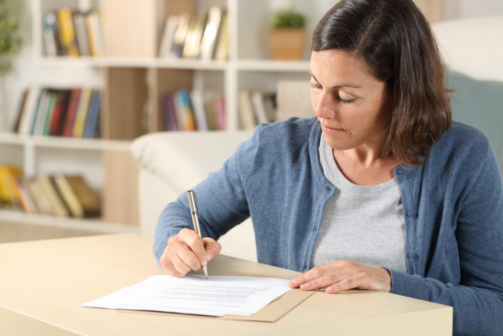 Serious Adult Woman Signing Document At Home