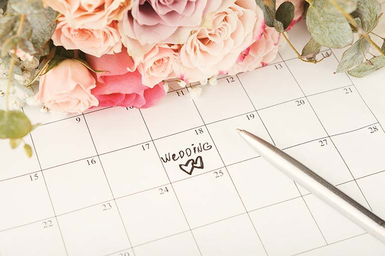 Word,wedding,and,two,hearts,on,calendar,with,sweet,rose