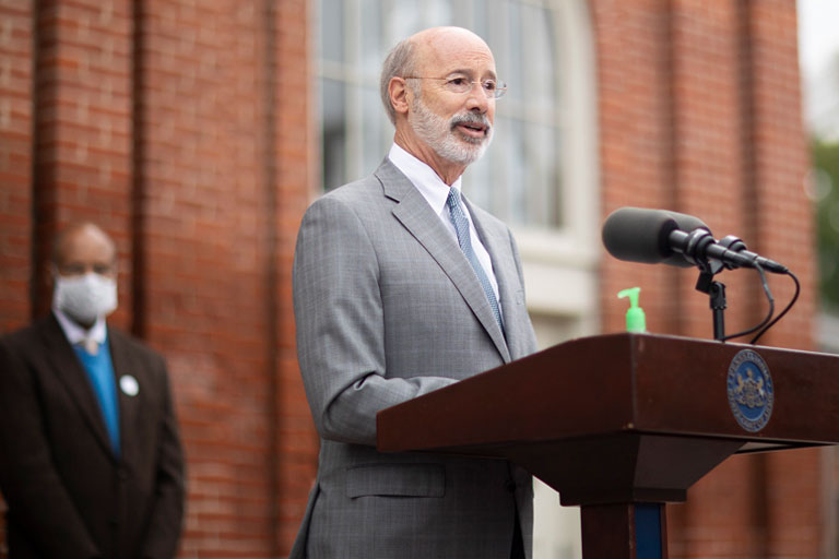 Govenor Wolf Speaking At A Podium Outside Of A Brick Building