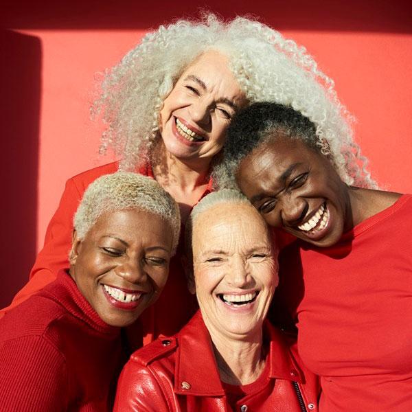 4 Women Smiling Wearing Red
