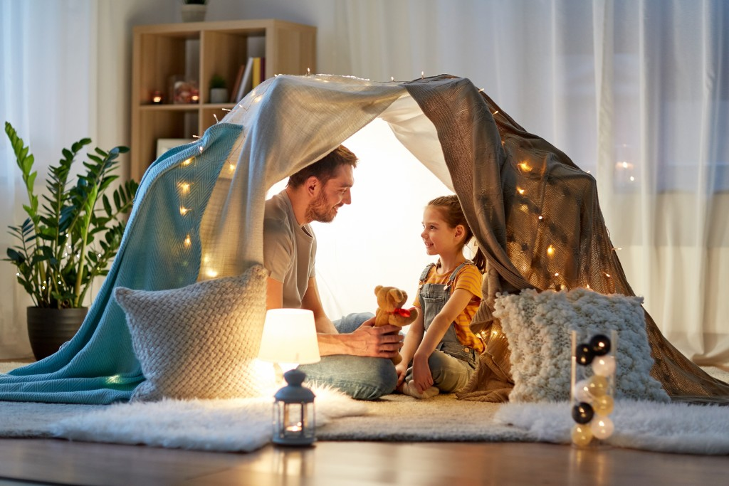 Happy Father Playing With Toy In Kids Tent At Home