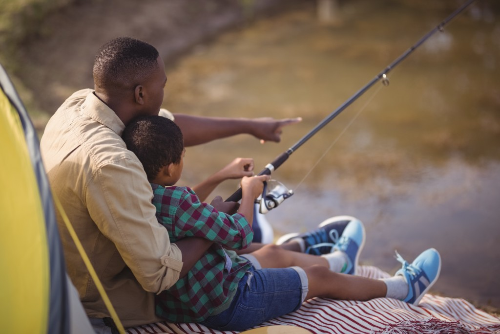 Father And Son Fishing Together In Park
