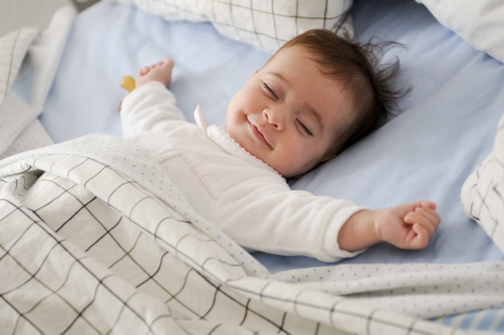 Smiling,baby,girl,lying,on,a,bed,sleeping,on,blue