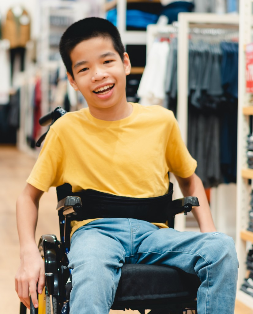 Disabled Child On Wheelchair Having Fun Shopping For Clothes Tha