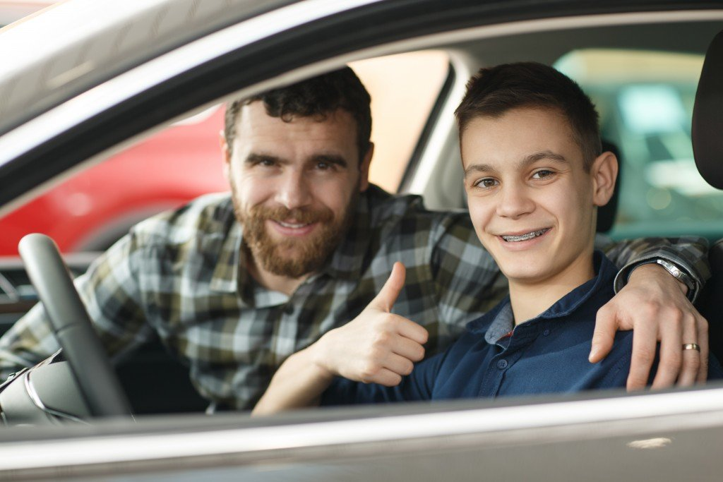 Handsome Mature Man And His Young Son Buying A New Automobile Together