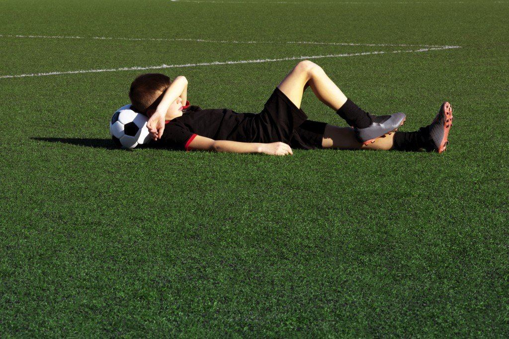 Cute Boy Soccer Player Lies On The Grass Of A Football Field, Resting After Training. Child Soccer Player And A Soccer Ball. Sport Concept. Kids Football School, Tournament. Background. Copy Space
