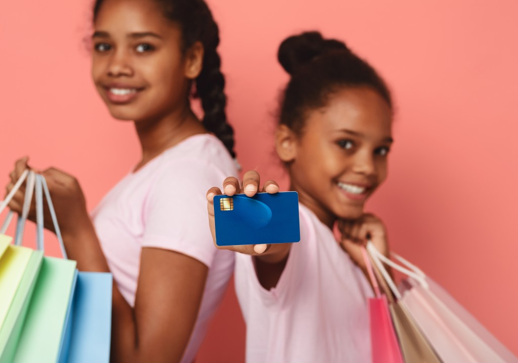 Smiling African Girls With Shopping Bags Recommending Credit Card