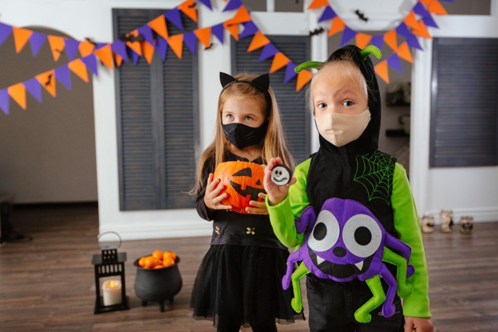 Children In Halloween Costumes And With Masks On Their Faces Play