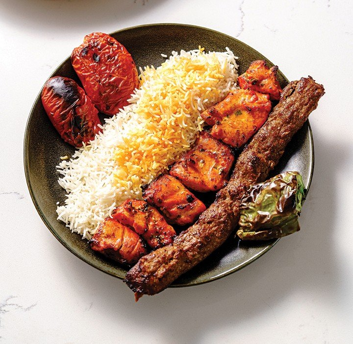 The joojeh soltani entrée with marinated chicken and ground sirloin kebabs, basmati rice, grilled tomatoes and roasted Anaheim pepper.