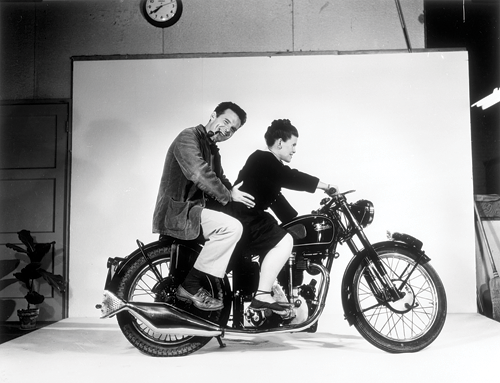 Charles and Ray Eames on a Velocette motorcycle at the Eames Office in Venice, Calif. (Photo courtesy of and © Eames Office, LLC)