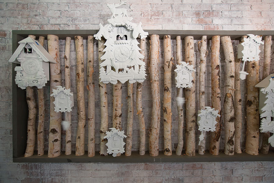 A crazy-cool wall of cuckoo clocks mounted on birch tree trunks